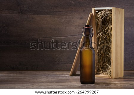 Craft beer bottle mock-up, beer bottle without label with a wooden gift box standing on a rustic table - stock photo