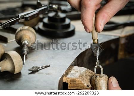 Craft jewelery making.  Repairing ring by inlaid tight gem. - stock photo