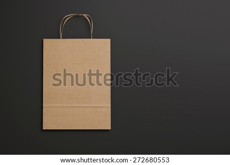 Craft paper bag with handles on black background. 3d render - stock photo
