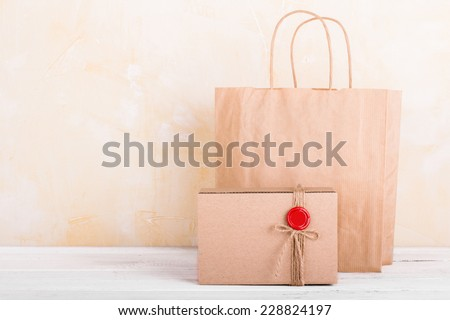Craft paper shopping bag and gift box on white wooden tabletop background - stock photo
