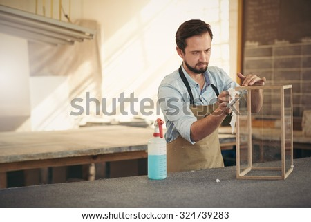 Craftsman designer concentrating while applying the finishing touches to a project in his woodwork workshop - stock photo
