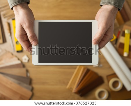 Craftsman holding a digital touch screen tablet hands close up, wood swatches and tools on background, top view - stock photo