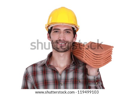 craftsman holding roof tiles - stock photo
