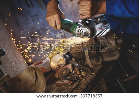 Craftsman sawing metal with disk grinder in workshop. Shallow depth of field. - stock photo