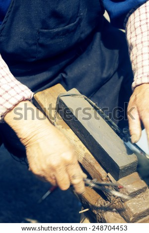 craftsman sharpen scissor with whetstone - stock photo