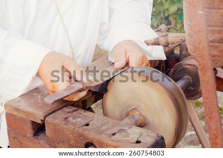 Craftsman sharpens an old knife on a wheel of the profession of an antique grinder - stock photo
