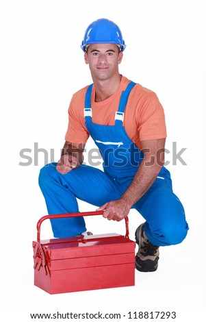 craftsman squatting with toolbox - stock photo