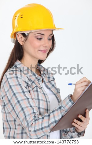 craftswoman holding a notepad and writing - stock photo