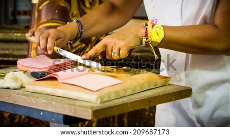 Craftswoman's hands cutting a gold leaf - stock photo