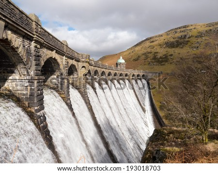 Craig Goch dam overflowing with water in the Elan Valley Wales UK. - stock photo