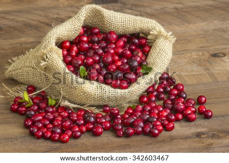 Cranberries in a bag on wooden background. - stock photo