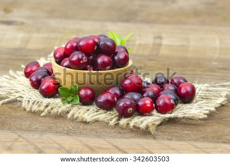 Cranberries in wooden bowl on wooden background. - stock photo