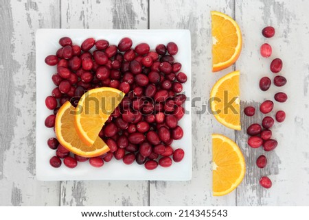 Cranberry and orange fruit over weathered wooden white background. - stock photo