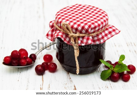 cranberry jam with fresh fruits on a old wooden background - stock photo