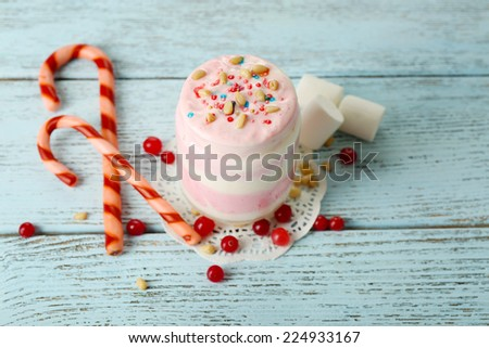 Cranberry milk dessert in glass and glass jar, on color wooden background - stock photo
