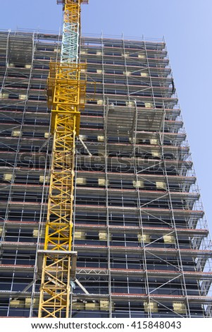 Crane and building construction site against blue sky. Big building construction. Inside place for many tall buildings under construction and cranes under a blue sky. - stock photo