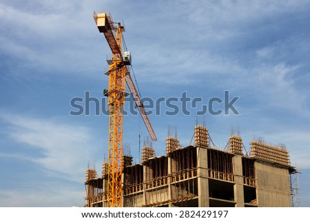 Crane and building house under blue sky - stock photo