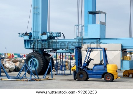 Crane and forklift in port - stock photo