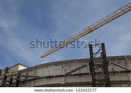 crane and top of construction building over blue sky - stock photo
