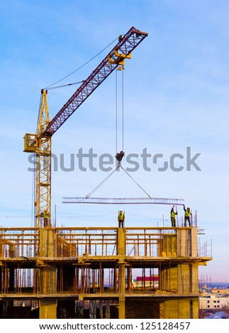 Crane and workers at  construction site against blue sky. - stock photo