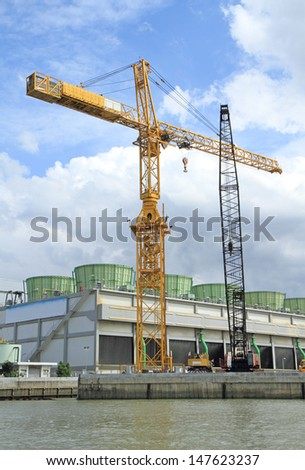 Crane at construction site by the river - stock photo