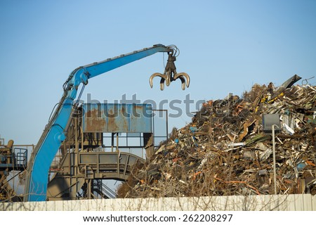 Crane claw on top of pile with scrap metal in recycling center - stock photo
