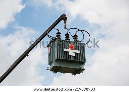 Crane hook lifts up distribution transformer - stock photo