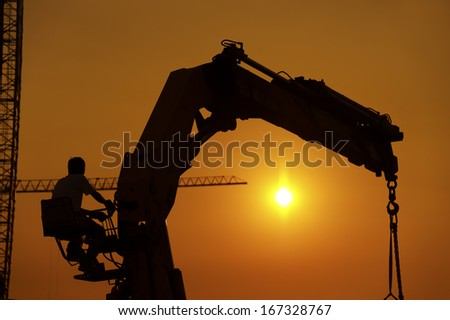 Crane in construction site under sunset - stock photo