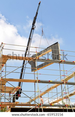 crane is pulling down a finished part into the construction site - stock photo