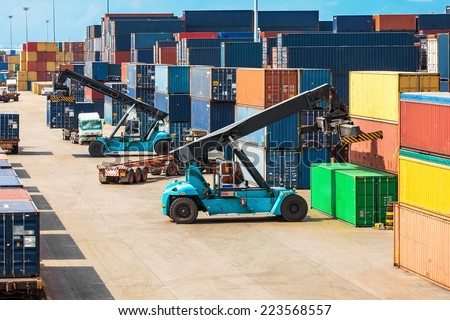 Crane lifter handling container box loading to truck in import export logistic zone - stock photo
