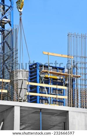 Crane lifting concrete mixer container against blue sky - stock photo