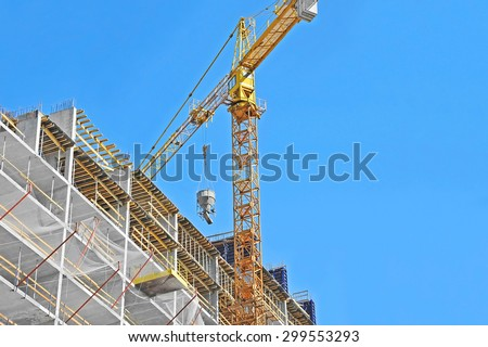 Crane lifting concrete mixer container against blue sky - stock photo