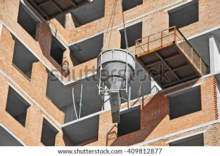 Crane lifting concrete mixer container on construction site - stock photo
