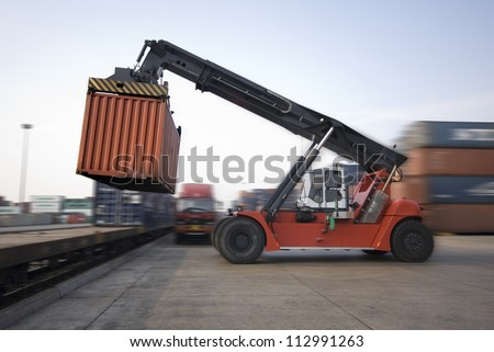 Crane lifting up container in railroad yard - stock photo
