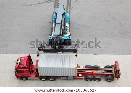 Crane moves and loads container to big truck, view from above - stock photo