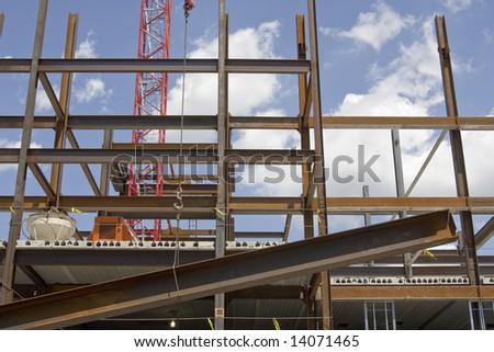 Crane pulling up steel beams for building framework - stock photo