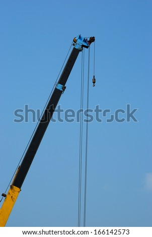 Crane working with blue sky background - stock photo