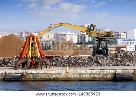 Crane working with scrap metal stored in port - stock photo