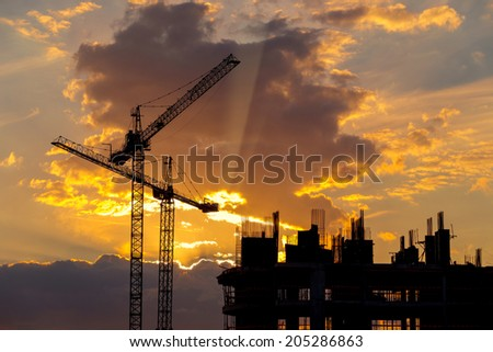 Cranes and building construction site against sunset sky - stock photo