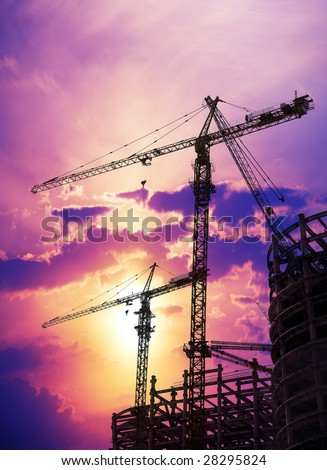 cranes and construction at sunset. - stock photo