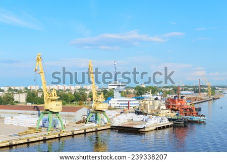 Cranes and vessels in cargo terminal - stock photo