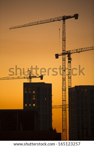 Cranes at sunset. Industrial construction cranes and building silhouettes over sun at sunrise. Vertical format - stock photo