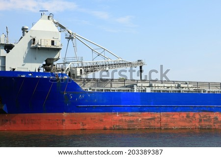 cranes in a port loading a ship coal - stock photo