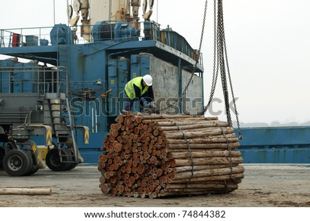 Cranes in a port, unloading a cargo timber ship, a cloudy day - stock photo