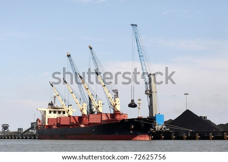 cranes in a port, unloading a ship - stock photo