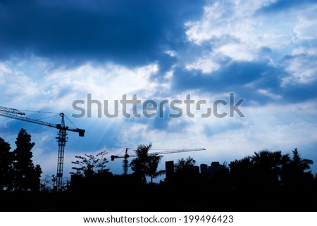 Cranes on a construction site at sunrise - stock photo