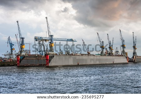 Cranes on a floating dock in Hamburg. Panorama floating dock with lots of cranes on background of the sky with clouds - stock photo