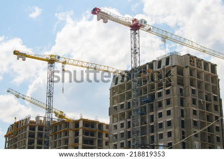 Cranes over unfinished buildings on construction site at a bright sunny day. - stock photo
