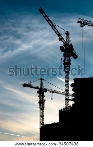 Cranes silhouettes and cloudy sky when sun goes down - stock photo