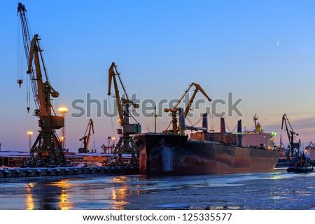 Cranes unloading a ship in a harbor - stock photo